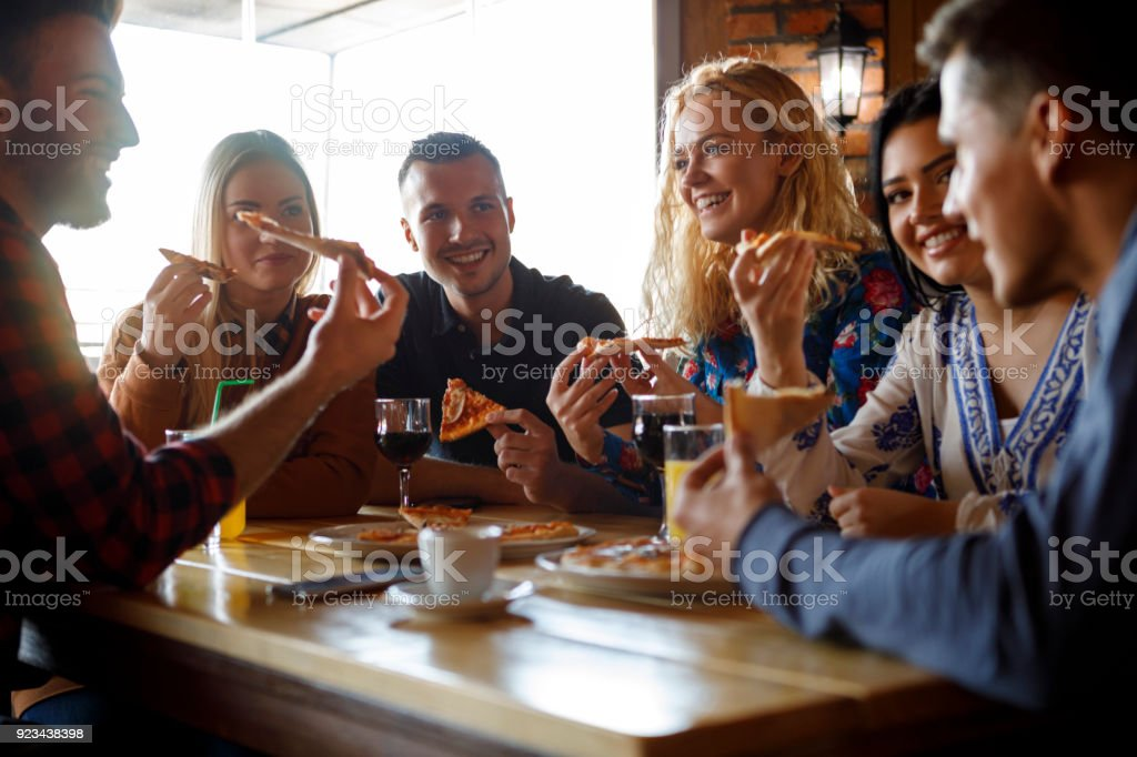 Grupo de amigos, comer pizza no restaurante - foto de acervo