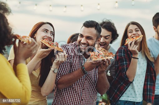Multi-ethnic group of young people eating pizza outdoors