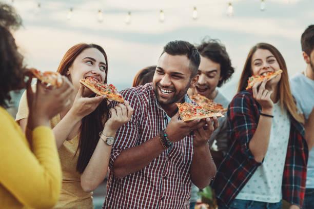 Grupo de amigos comendo pizza - foto de acervo