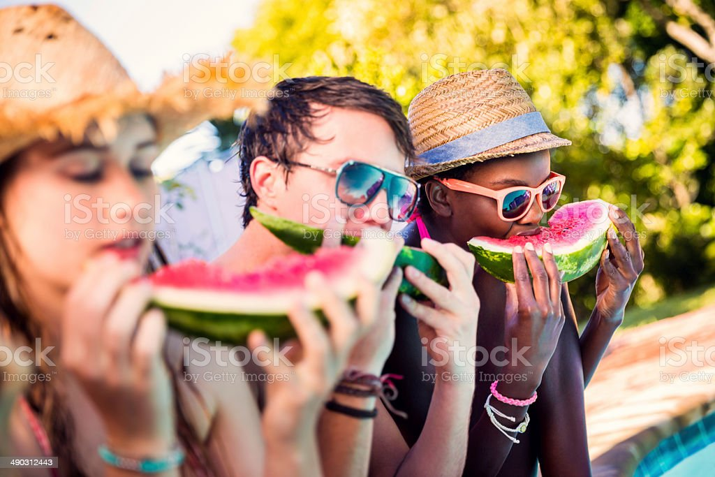 Group of friends eating watermelon stock photo