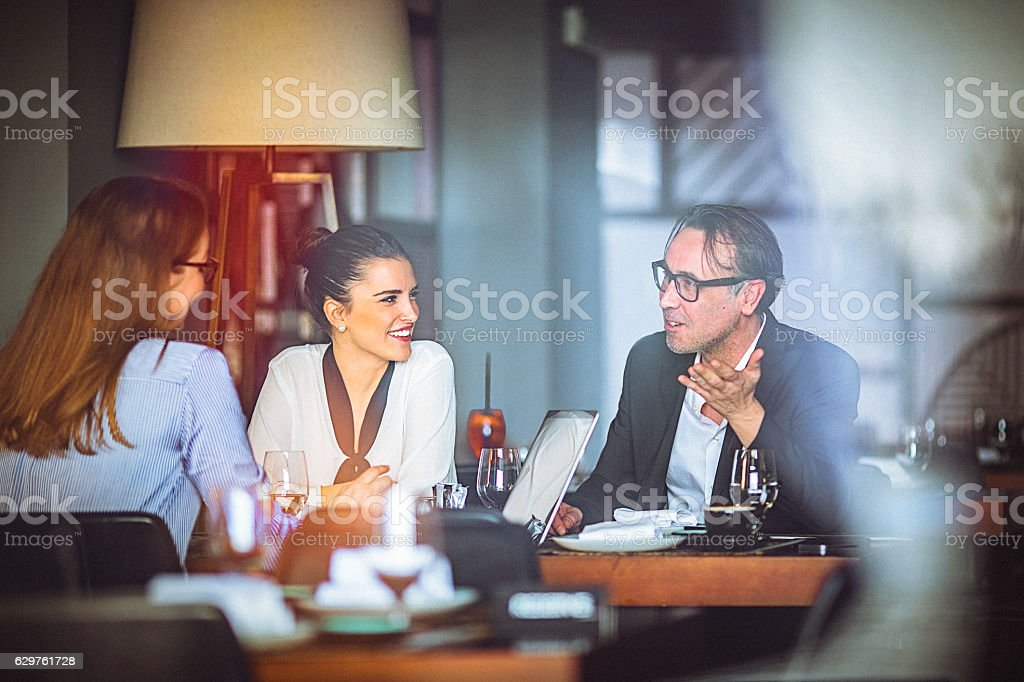 Group of friends enjoy chatting during lunch time at restaurant stock photo
