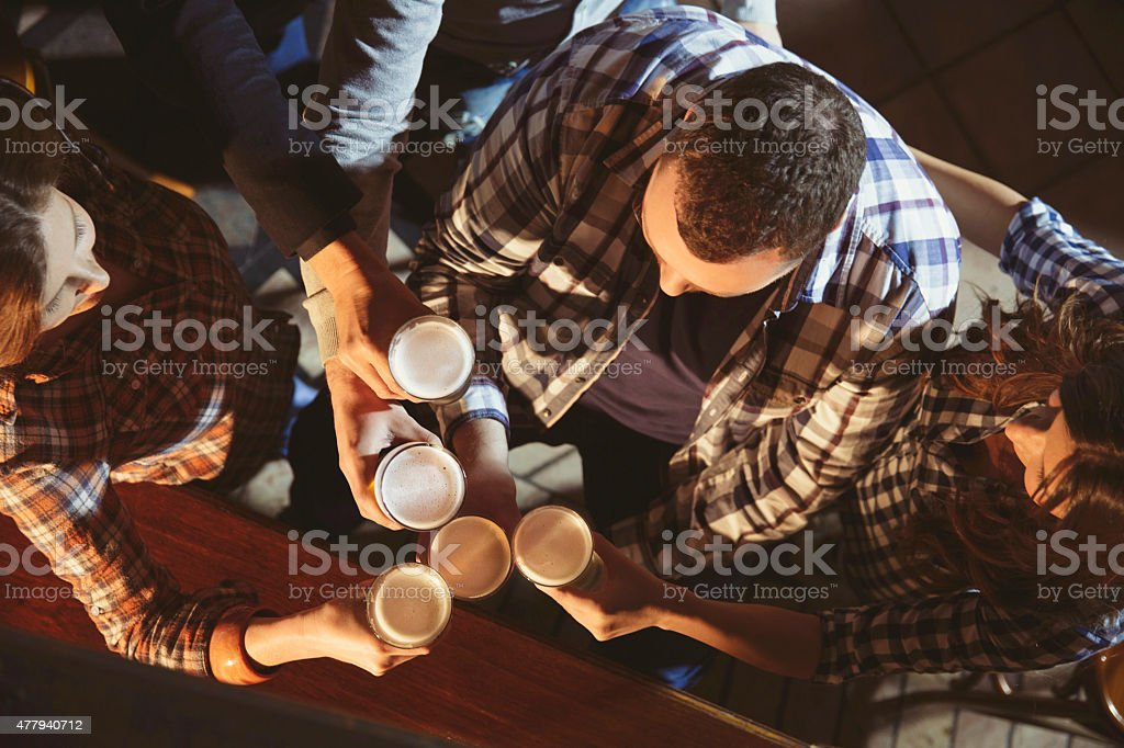 Group of friends enjoyin   Drinking beer  in the old pub stock photo