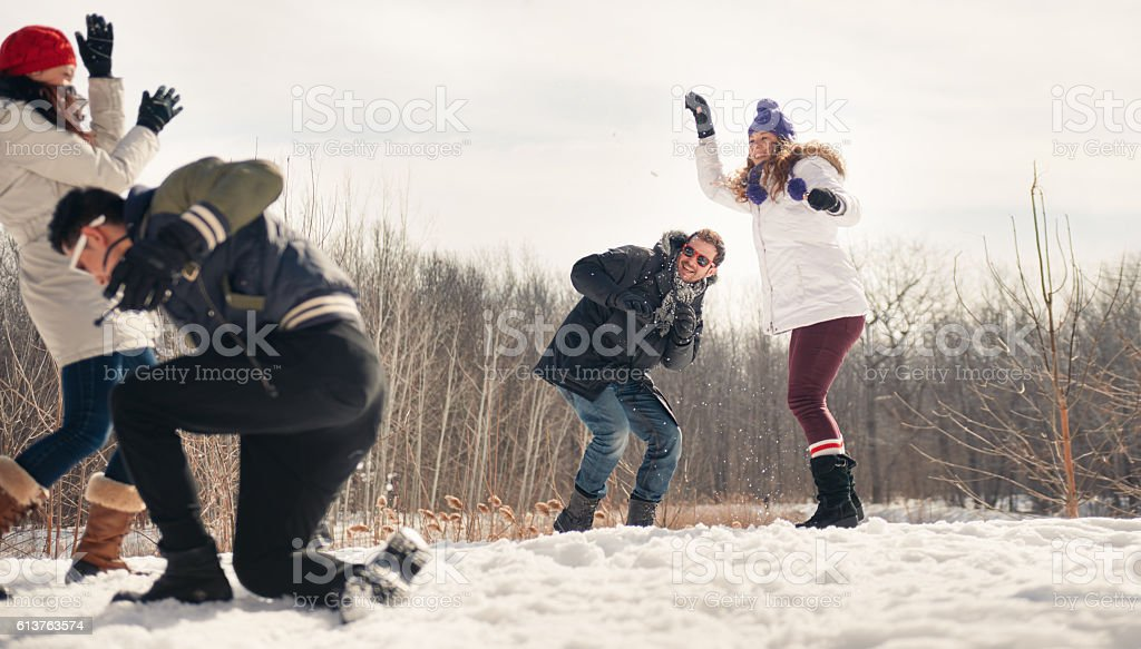 Group of friends enjoying a snowball fight in the snow - Photo