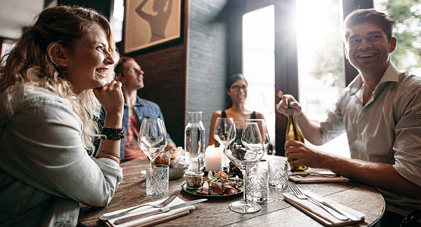 Group of friends enjoying an evening meal at a restaurant stock photo