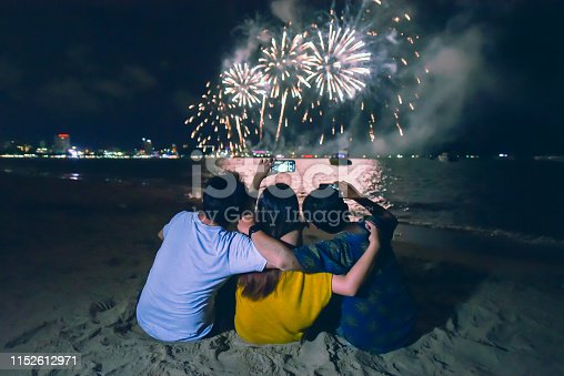 istock group of friends enjoying and holding the smartphone taking picture of colorful fireworks display over the beach with the night sky background 1152612971