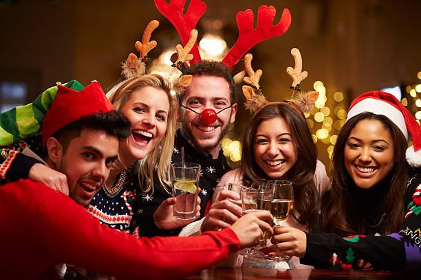 gruppe von freunden genießen sie weihnachten getränke in der bar - nikolaus kostüm stock-fotos und bilder