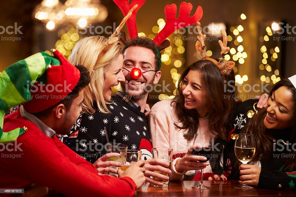 Group Of Friends Enjoying Christmas Drinks In Bar royalty-free stock photo