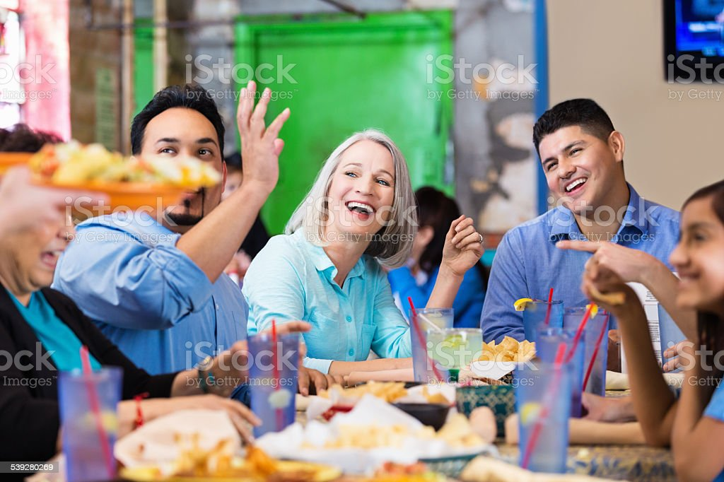 Group of friends enjoying dinner together in casual restaurant stock photo