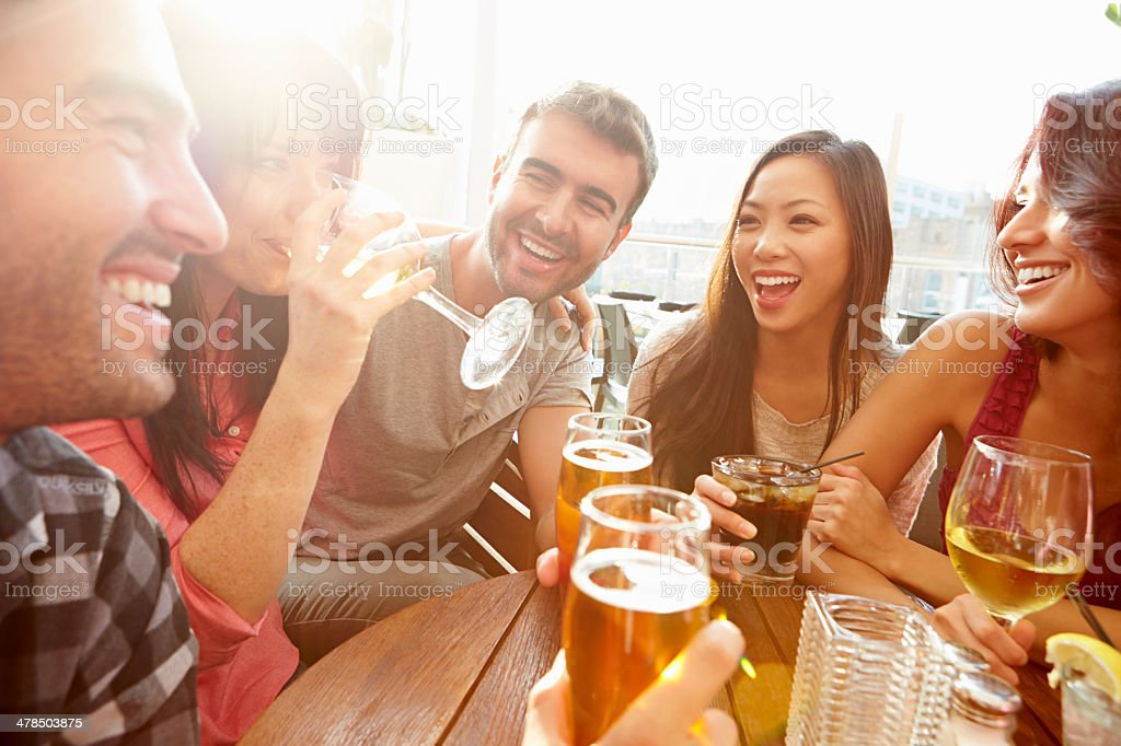 Group Of Friends Enjoying Drink At Outdoor Rooftop Bar royalty-free stock photo