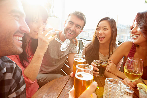 group of friends enjoying drink at outdoor rooftop bar - happy hour stock photos and pictures