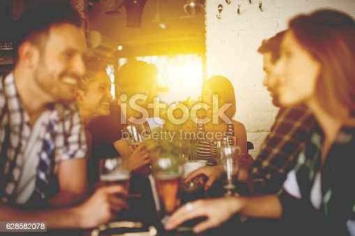 A group of friends met up at a pub for a drink after a long and busy day. they enjoy having a good time together. Having left all the worries aside they laugh at each other's jokes and  talk about new things that happened that day while drinking big glasses of beer.