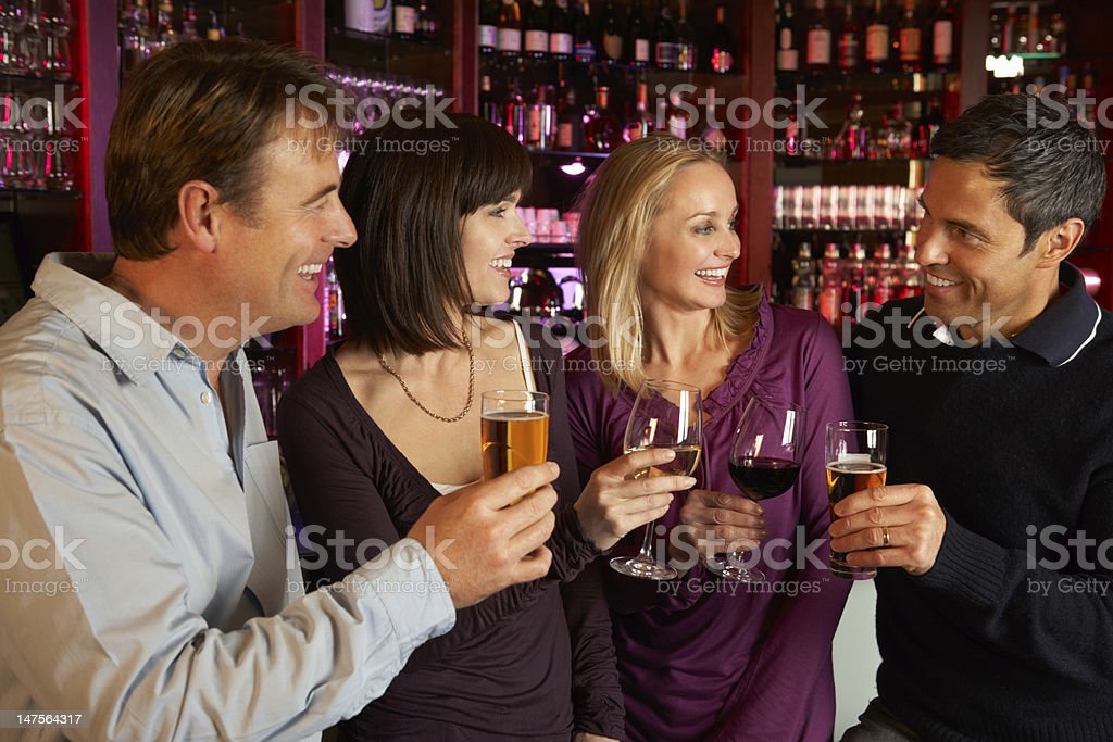 Group Of Friends Enjoying Drink Together In Bar royalty-free stock photo