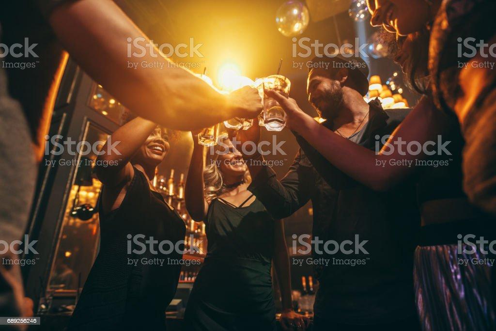 Grupo de amigos disfrutando de bebidas en el bar - foto de stock