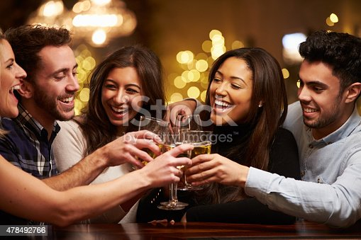 istock Group Of Friends Enjoying Evening Drinks In Bar 478492766