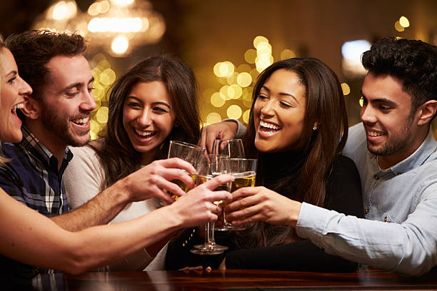 group of friends enjoying evening drinks in bar - happy hour stock photos and pictures