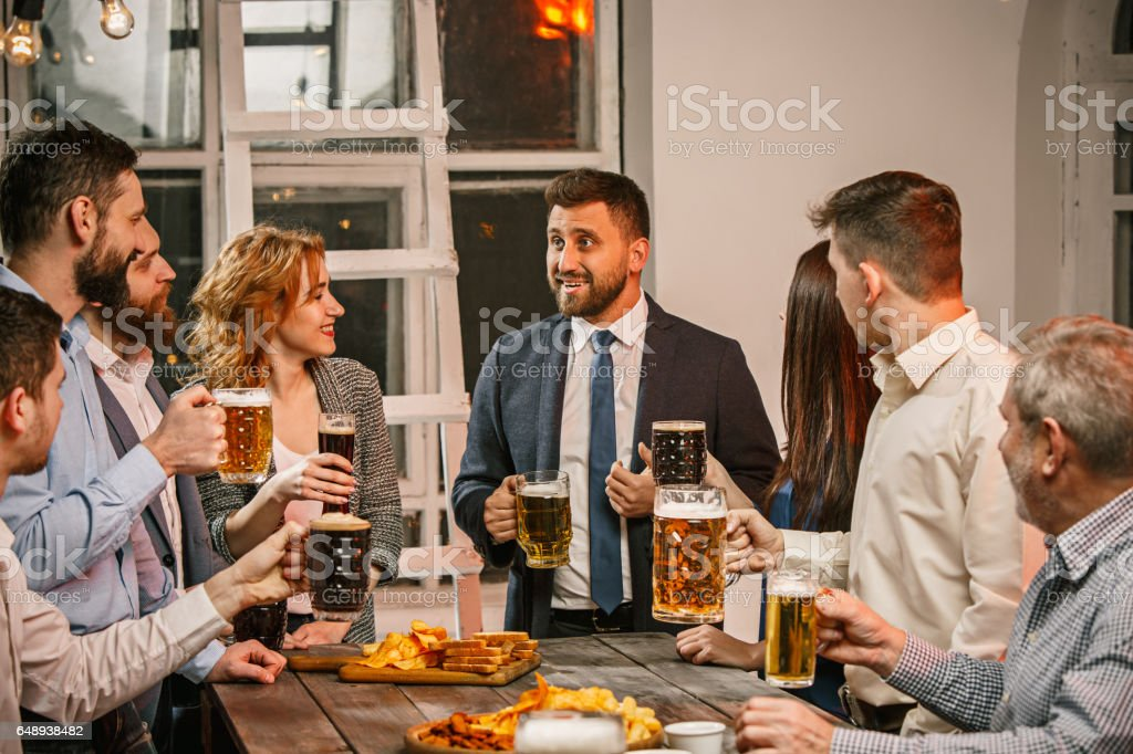 Group of friends enjoying evening drinks with beer - foto stock
