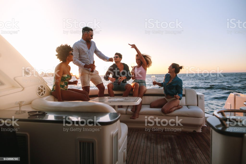 Group of friends enjoying in a boat party stock photo