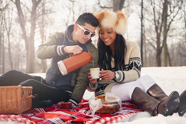 group of friends enjoying in the snow in winter - romantisches picknick stock-fotos und bilder