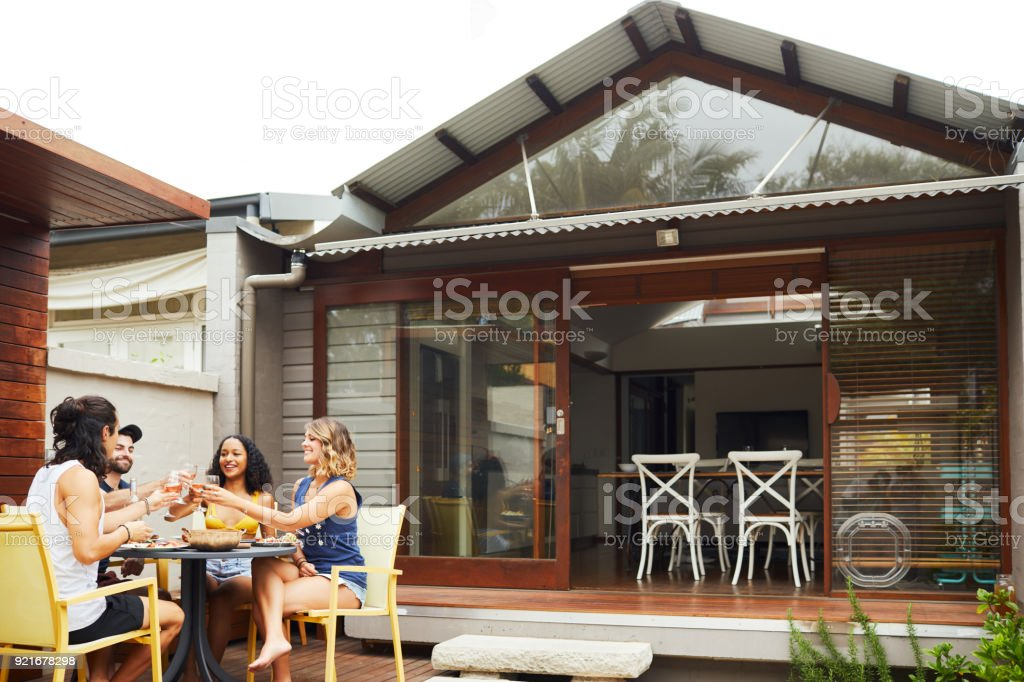 Group of friends enjoying lunch and barbecue in backyard. stock photo