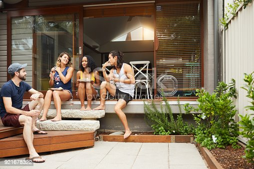 istock Group of friends enjoying lunch and barbecue in backyard. 921678322