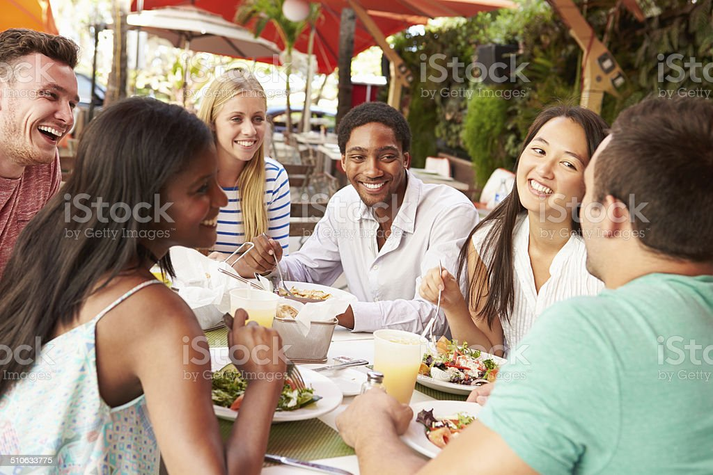 Group Of Friends Enjoying Lunch In Outdoor Restaurant Smiling