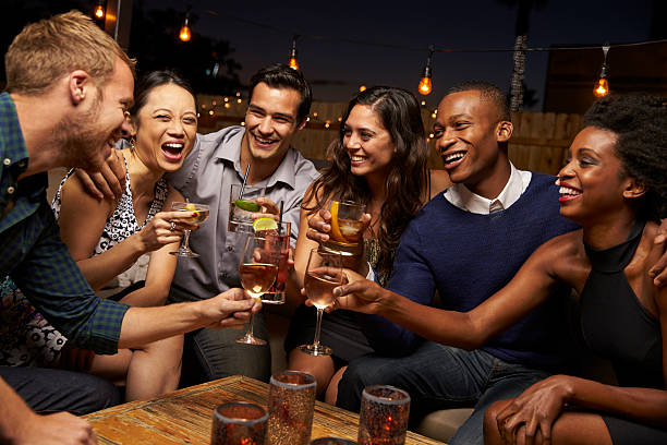 group of friends enjoying night out at rooftop bar - couple lap stock photos and pictures
