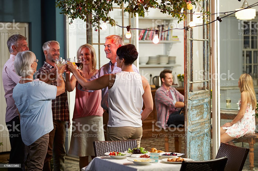 Group Of Friends Enjoying Outdoor Evening Drinks Party stock photo