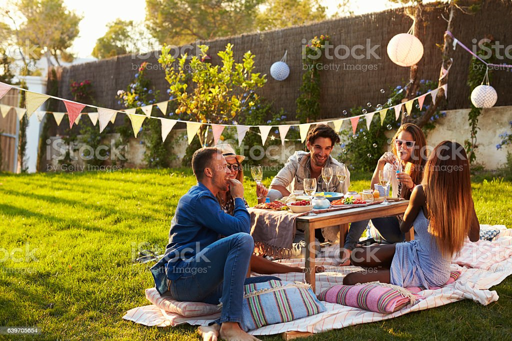 Group Of Friends Enjoying Outdoor Picnic In Garden - foto de stock