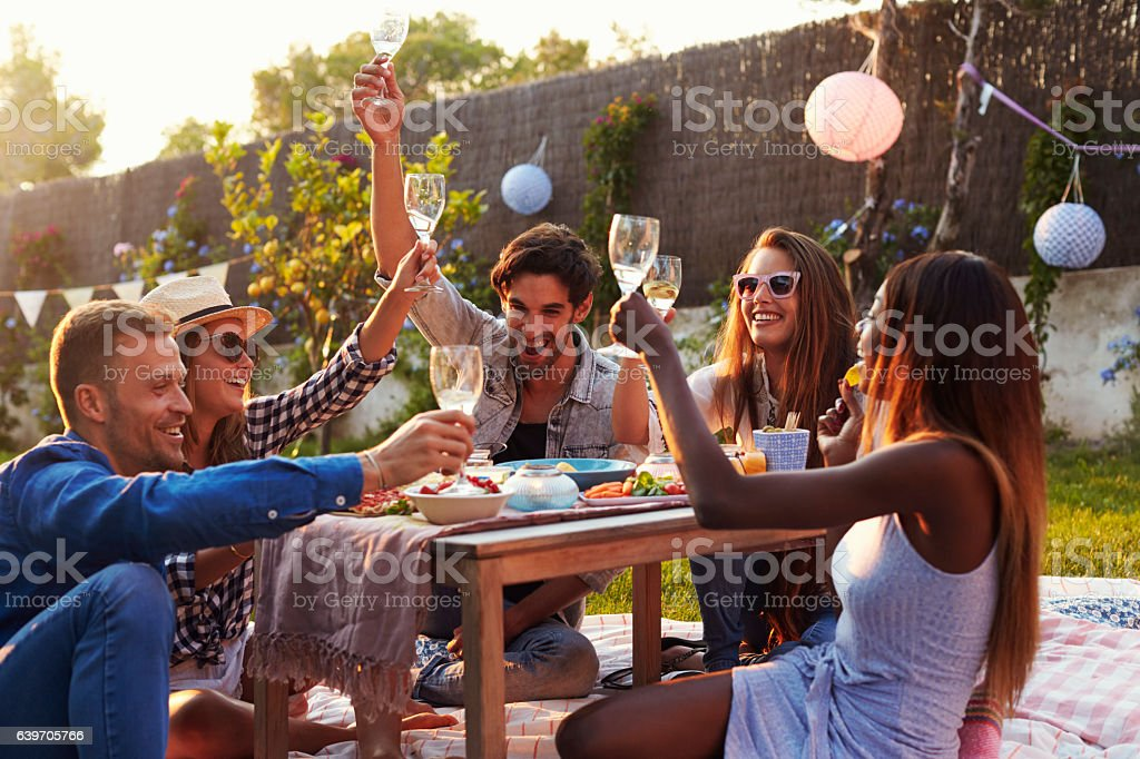 Group Of Friends Enjoying Outdoor Picnic In Garden - foto de acervo