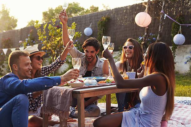 Group Of Friends Enjoying Outdoor Picnic In Garden - foto de acervo