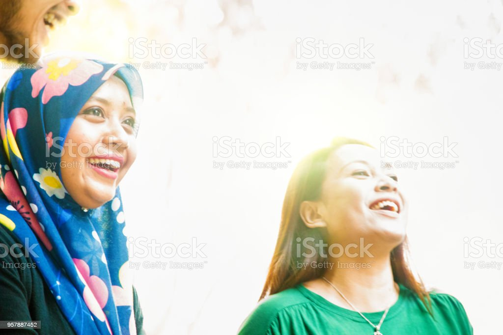 Group of friends enjoying outdoors including a young Muslim female stock photo