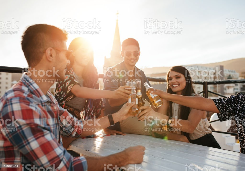 Group of friends enjoying party with drinks stock photo