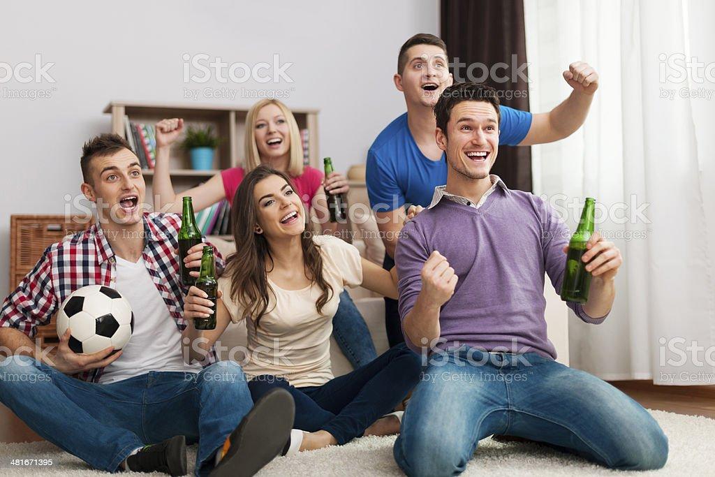 Grupo de amigos disfrutando de fútbol en televisión - foto de stock