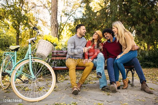 Young beautiful multiethnic couple having fun with their bike, smiling, talking and sitting on the bench