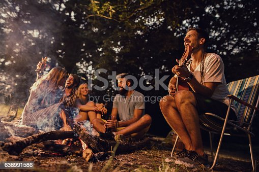 Young man sitting by the bonfire and playing acoustic guitar while his friends are having fun in the background.
