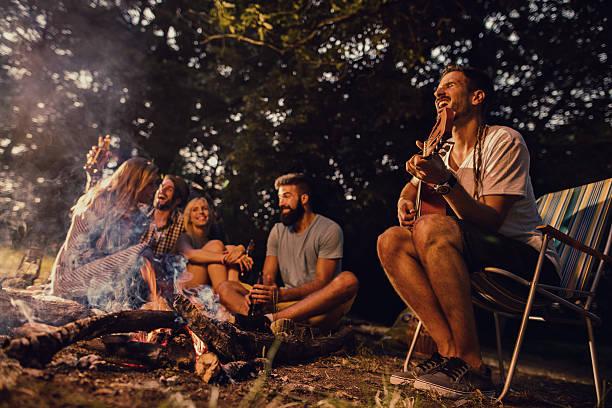 group of friends enjoying with music around campfire in nature. - bos spelen stockfoto's en -beelden