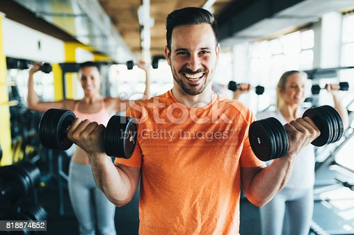 istock Group of friends exercising together in gym 818874652