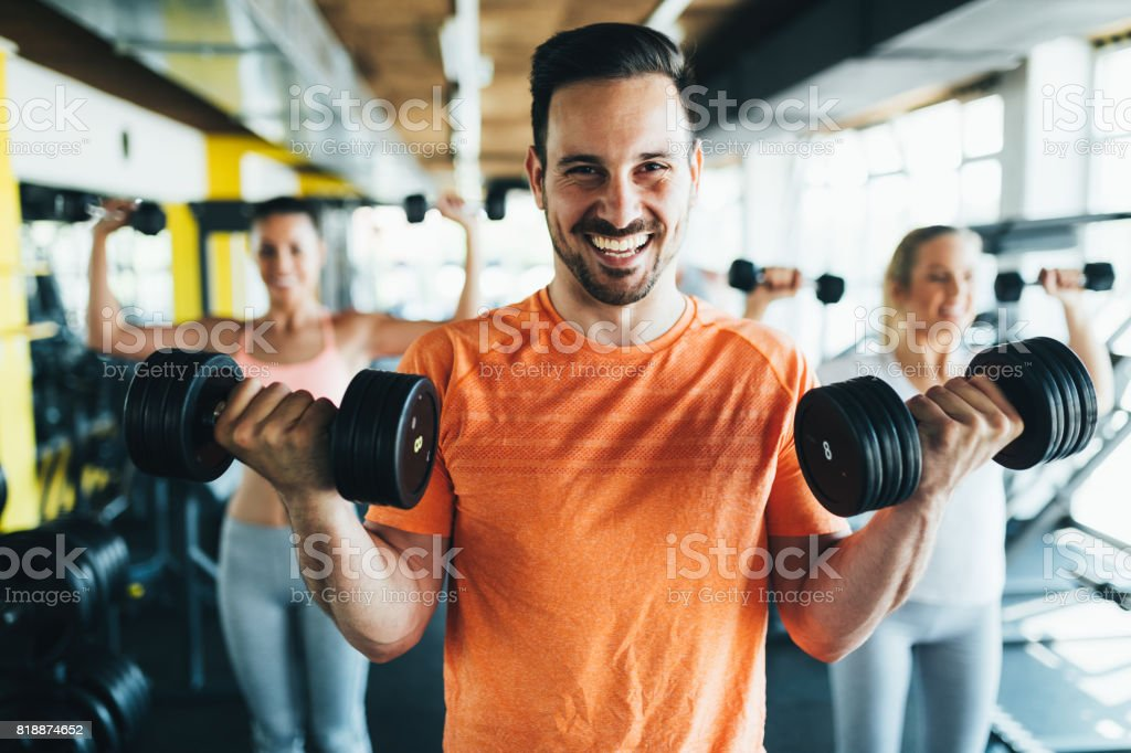 Group of friends exercising together in gym stock photo