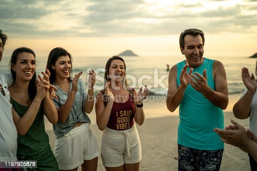 815703312 istock photo Group of friends / family applauding at beach 1197925878