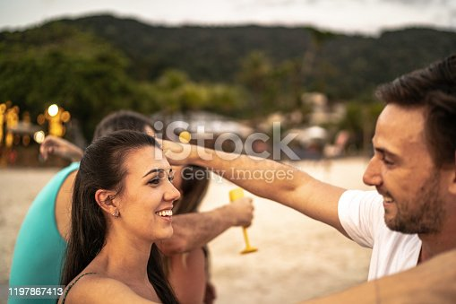 istock Group of friends / family embracing and celebrating at beach 1197867413