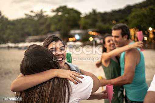 Group of friends / family embracing and celebrating new year at beach