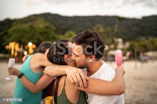 istock Group of friends / family embracing and celebrating new year at beach 1197870133