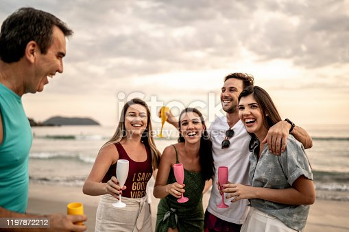 istock Group of friends / family embracing and celebrating new year at beach 1197872212