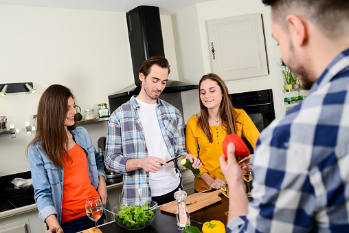 Group Of Friends Four People Man And Woman At Home Cooking