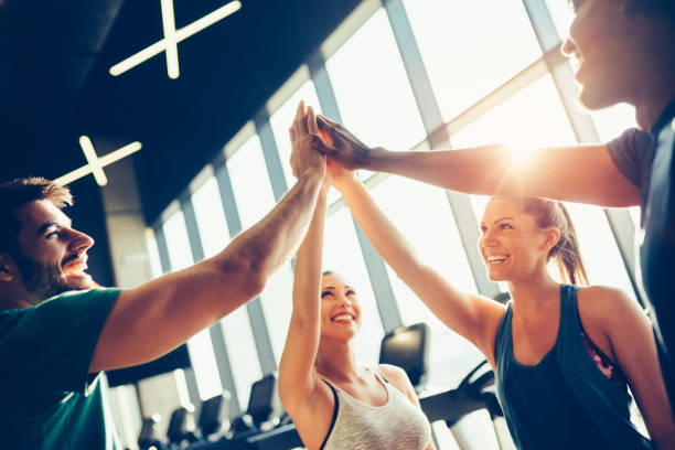 Group of friends giving high five at gym stock photo