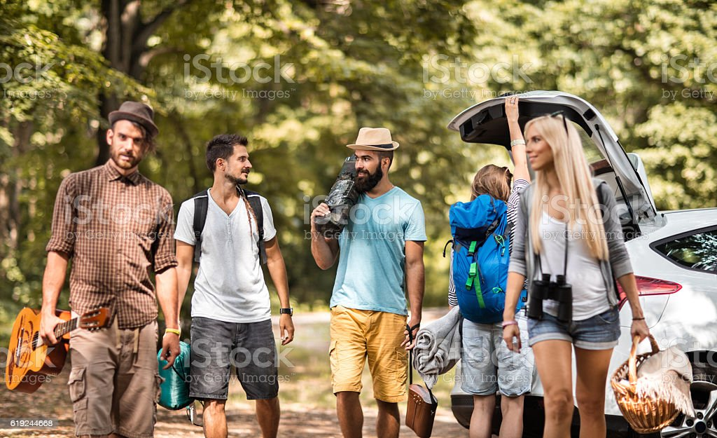 Group of friends going on camping in the forest. stock photo