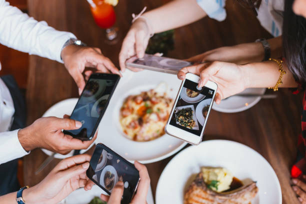 group of friends going out and taking a photo of italian food together with mobile phone. - foodie stock photos and pictures