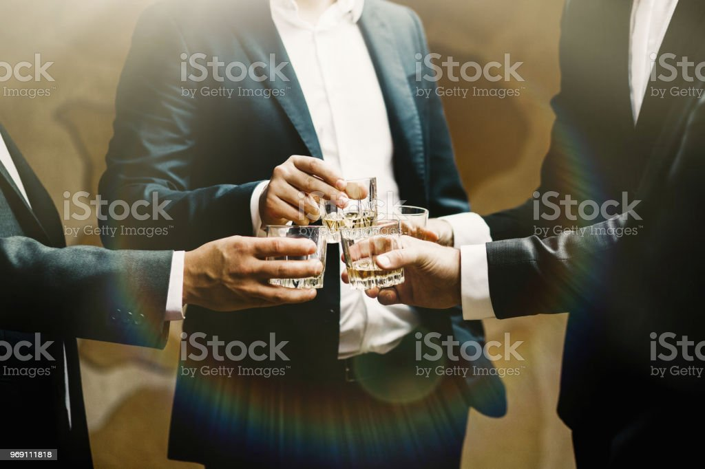 Group of friends guys with glasses of whiskey stock photo