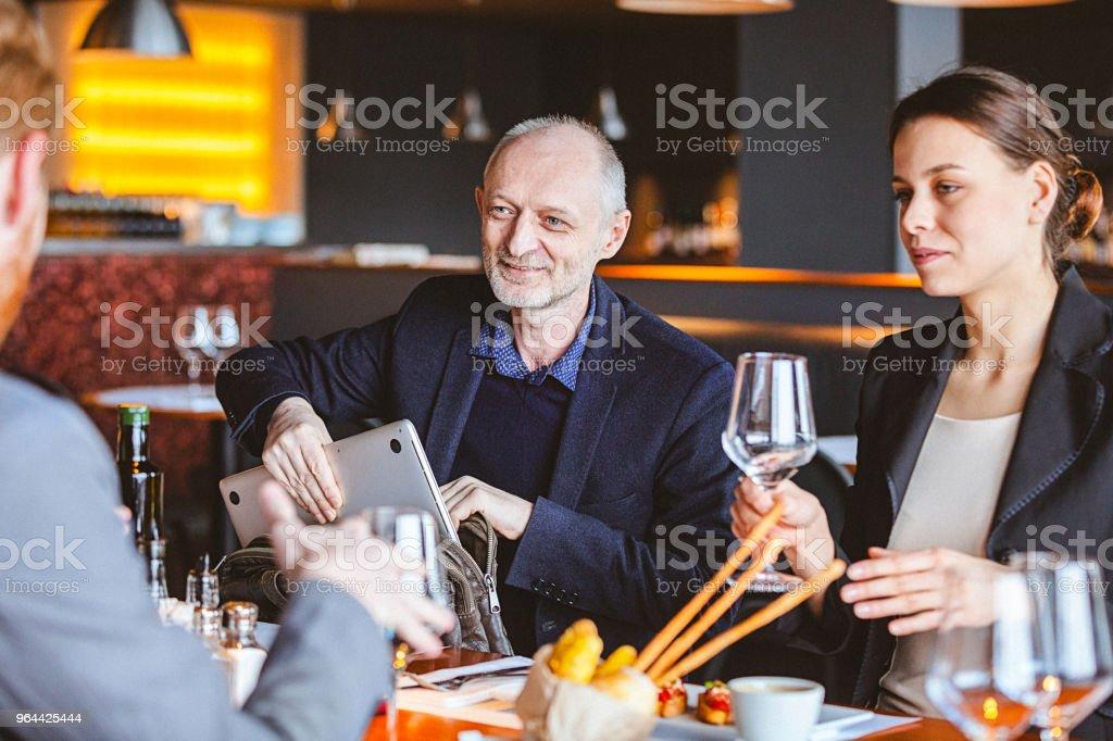 Grupo de amigos a ter uma conversa durante a hora do almoço em um café / restaurante - Foto de stock de 30 Anos royalty-free
