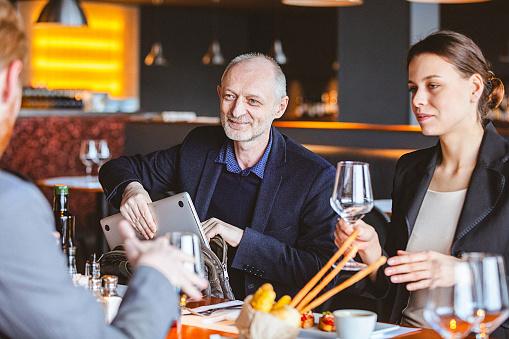 Foto de Grupo De Amigos A Ter Uma Conversa Durante A Hora Do Almoço Em Um Café Restaurante e mais fotos de stock de 30 Anos